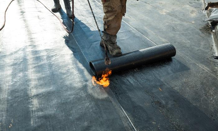 Mężczyzna kładący papę termozgrzewalną na dachu